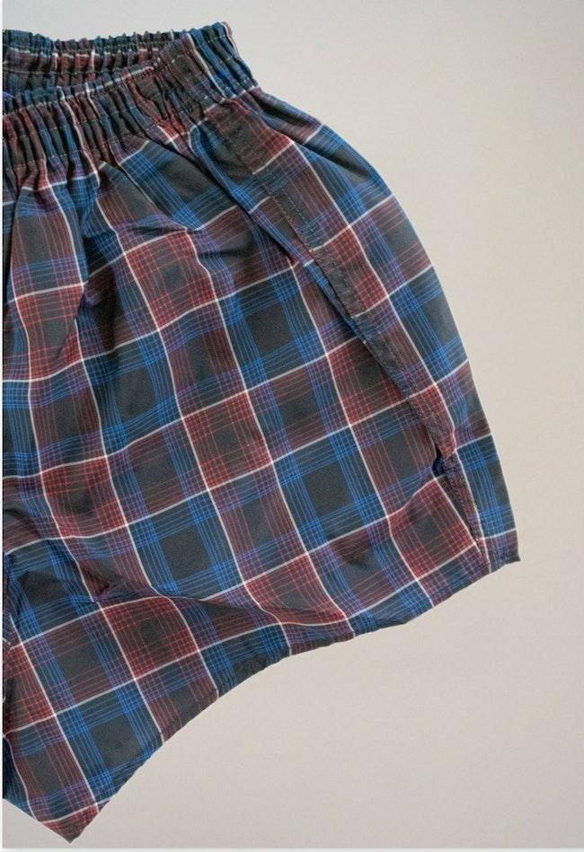 Short de bain noir à carreaux rouges et bleus / 8 ans